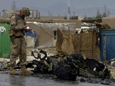 A Canadian soldier takes note over the wreckage of a suicide bomber's vehicle after the attack near Kandahar.